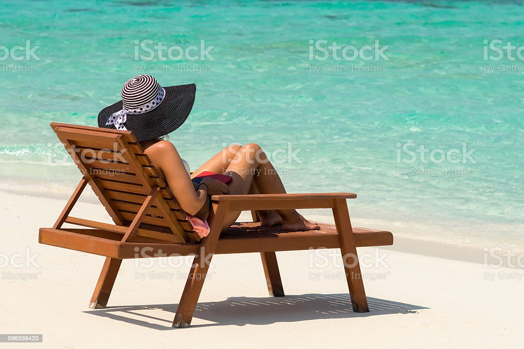 Young woman sunbathing on lounger at tropical beach stock photo