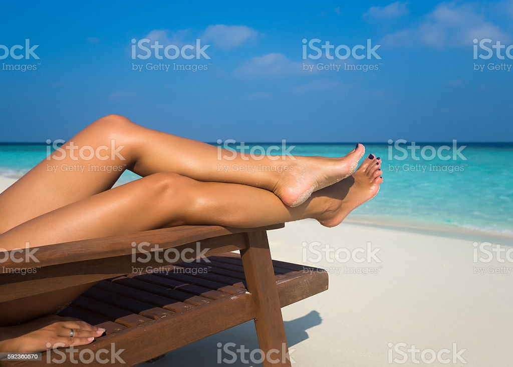 Young woman sunbathing on lounger. Legs. stock photo