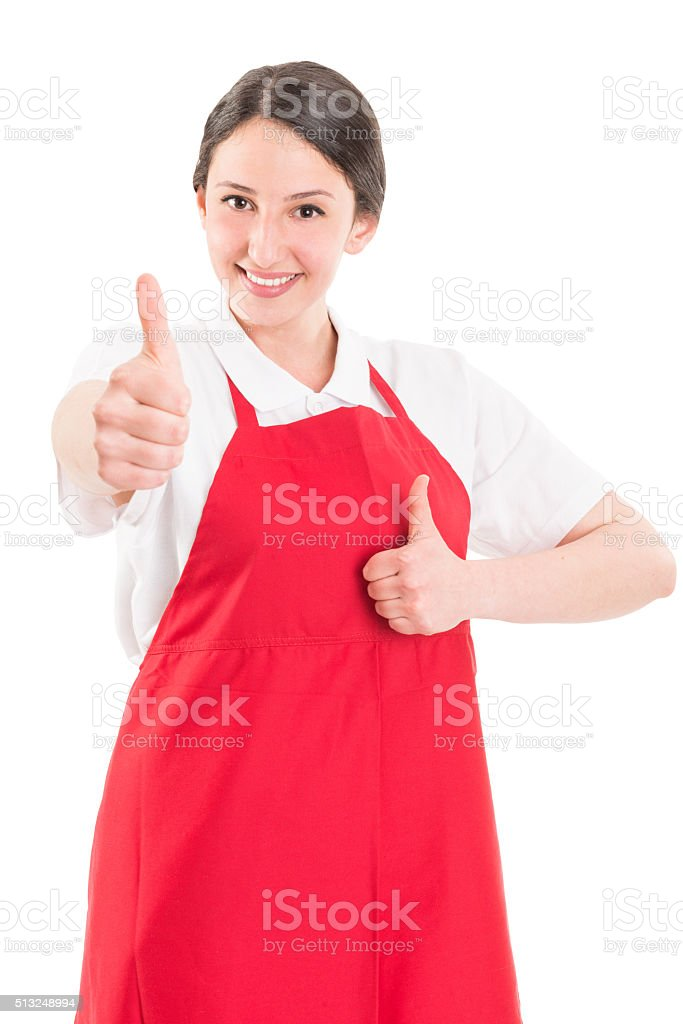 Young woman supermarket employee showing thumbs up stock photo