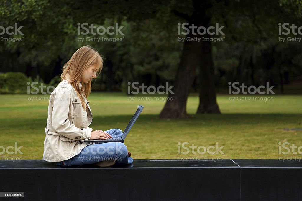 young woman surfing the internet in a park royalty-free stock photo