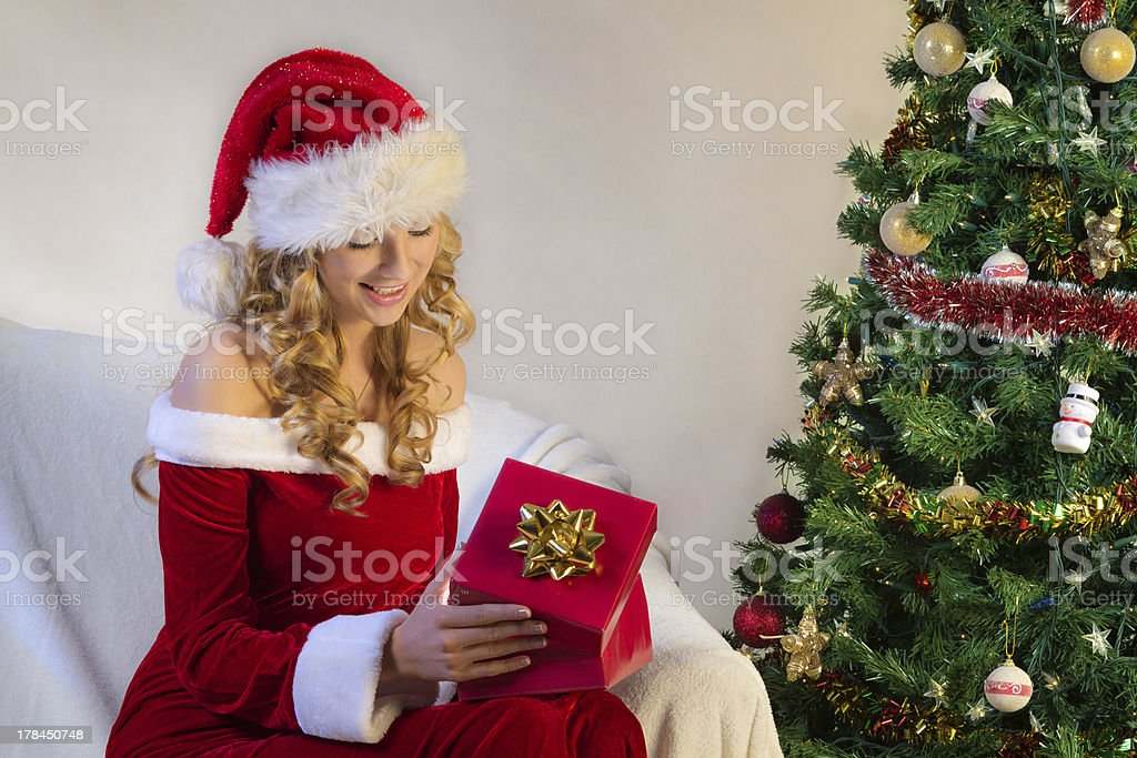 Young woman surprise when opening christmas gift royalty-free stock photo