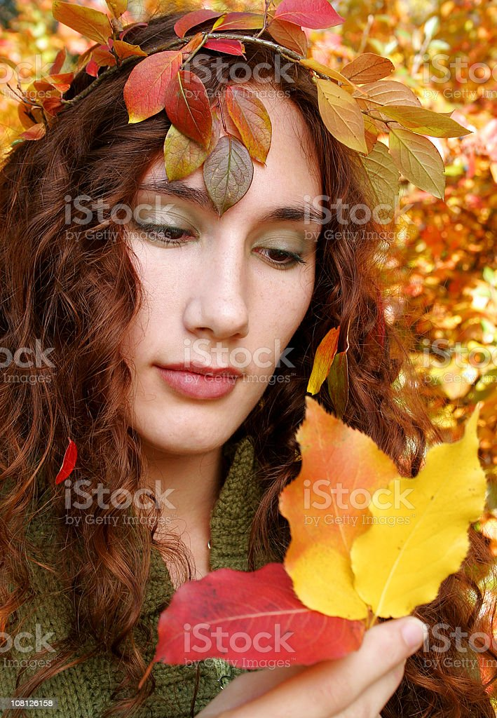 Young Woman Surrounded by and Holding Autumn Leaves royalty-free stock photo
