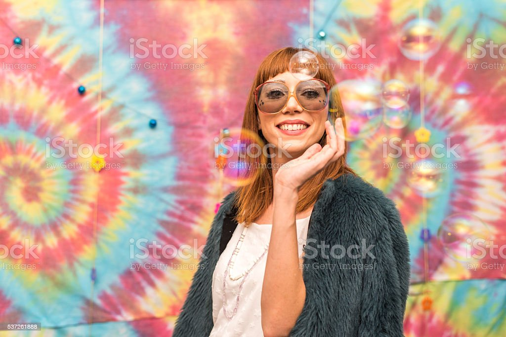 Young woman surrounded by floating bubbles stock photo