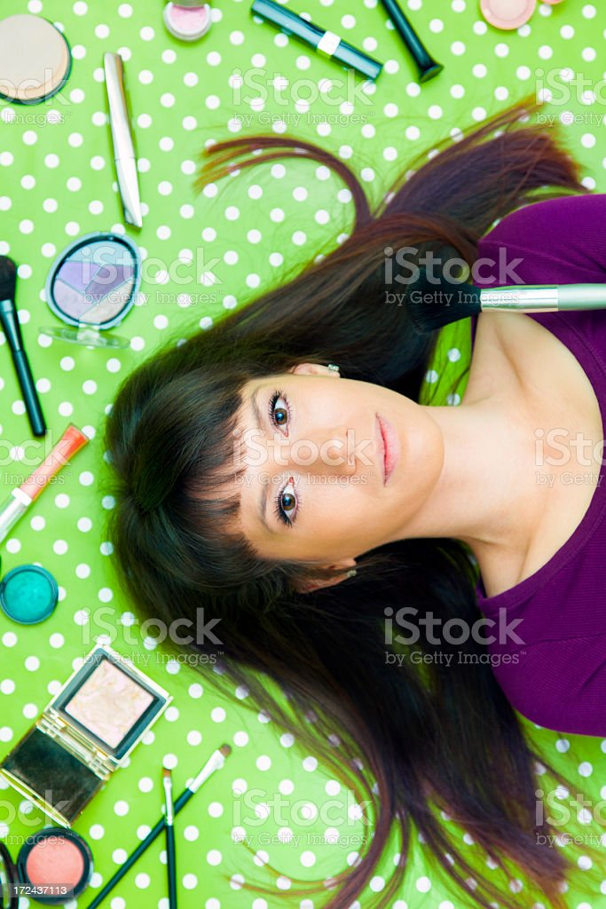 Young woman surrounded by make-up products royalty-free stock photo