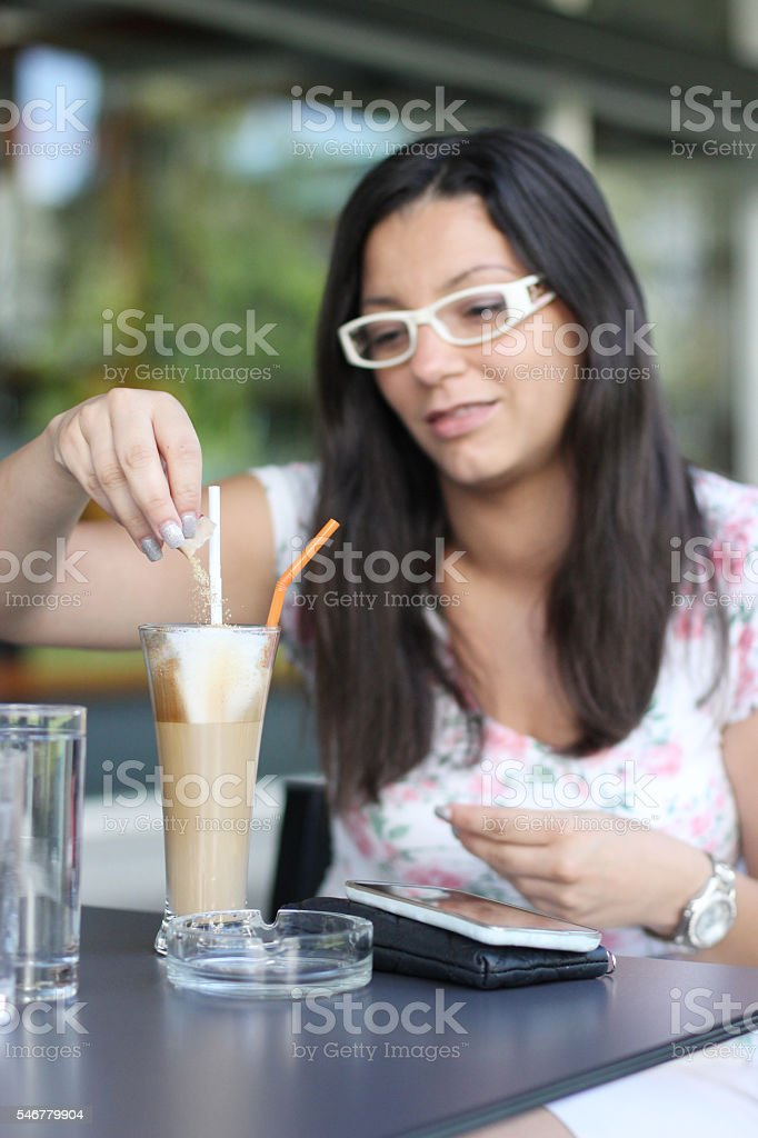 Young woman sweetening her coffee stock photo