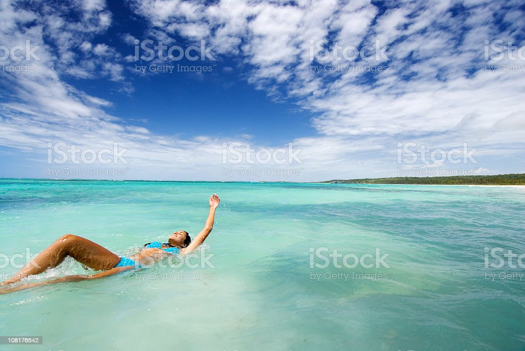 Young Woman Swimming Backwards in Tropical Ocean royalty-free stock photo