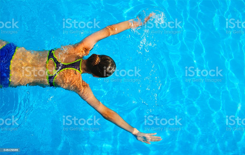Young woman swimming in a blue water pool stock photo