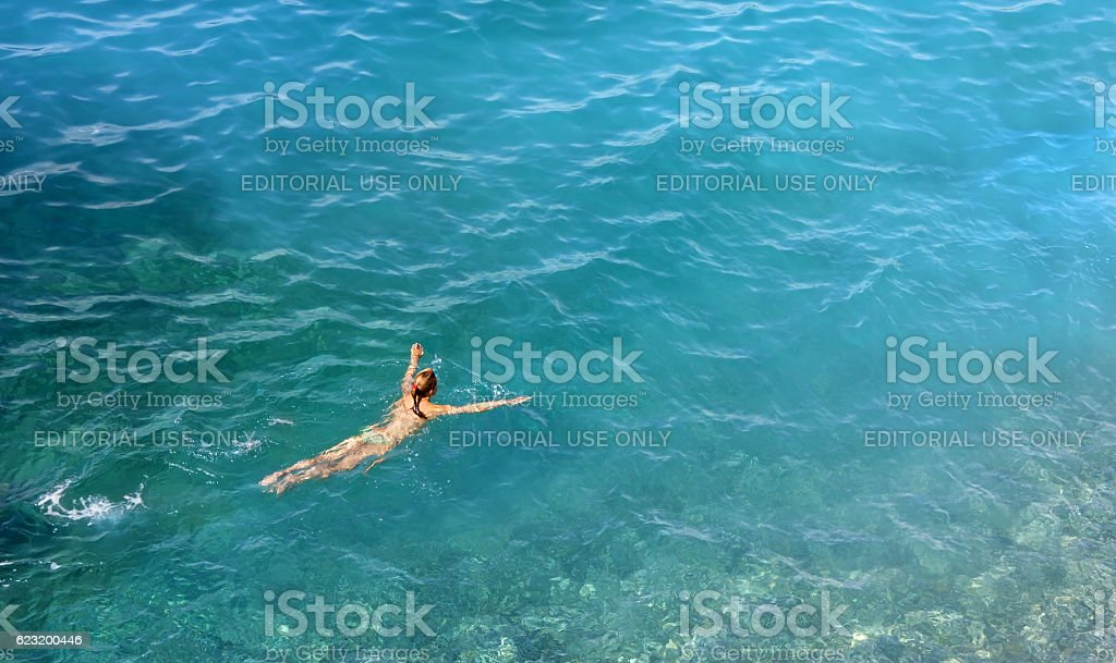 Young Woman Swimming in a Tuquoise Water stock photo