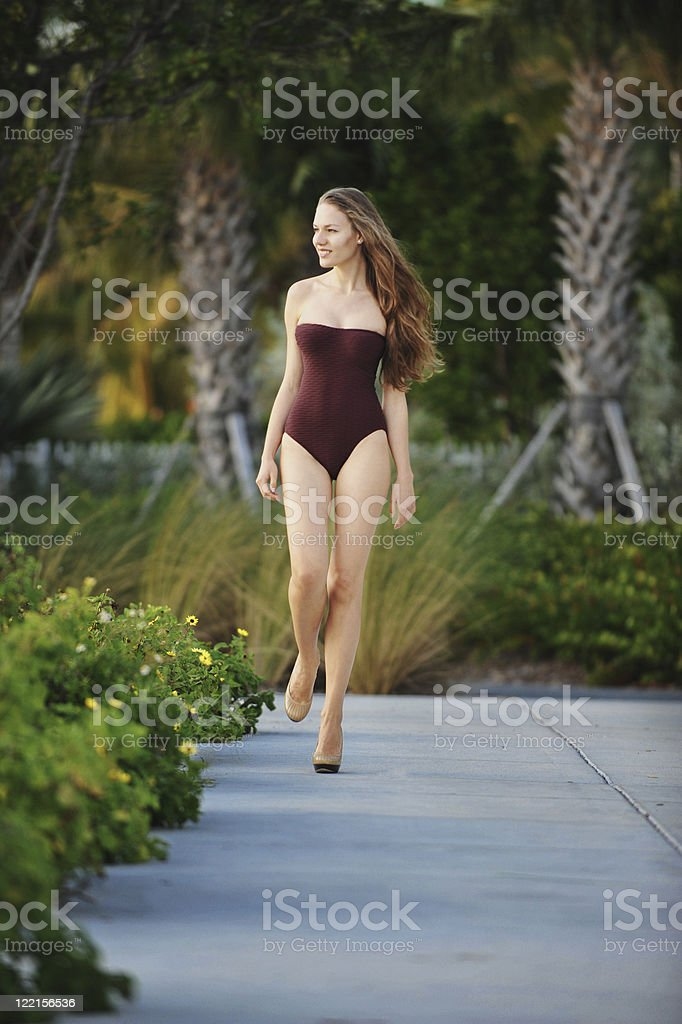 Young woman swimsuit model gazing out at sunset stock photo