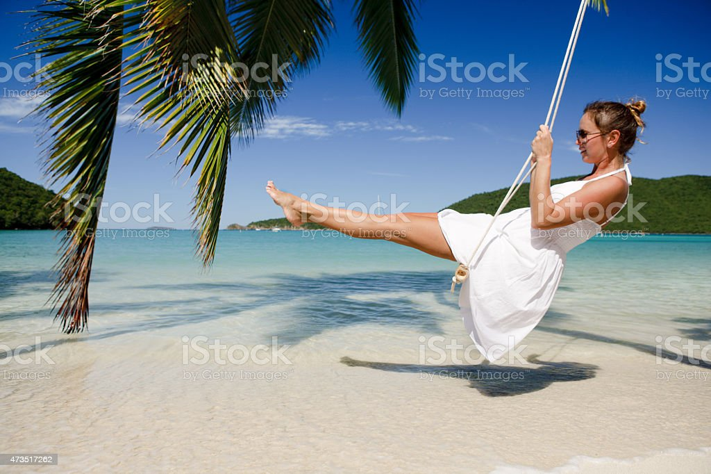 young woman swinging at a tropical beach in the Caribbean stock photo