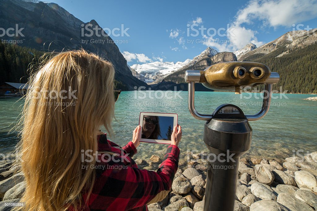 Young woman takes digital tablet pic beside viewer, mtns stock photo