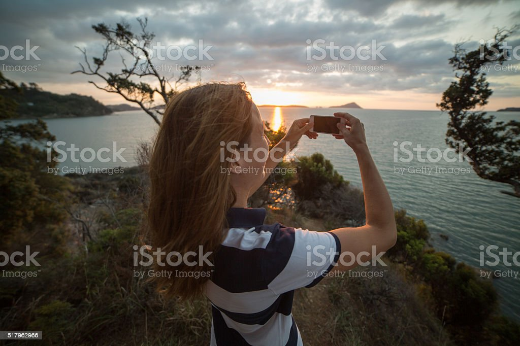 Young woman takes picture of beautiful landscape of Hauraki Gulf stock photo