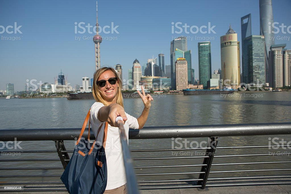 Young woman takes self portrait in Shanghai with selfie stick stock photo