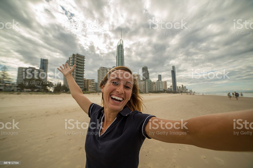 Young woman takes selfie portrait at Surfer's paradise beach stock photo