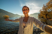 Young woman takes selfie portrait by the lake