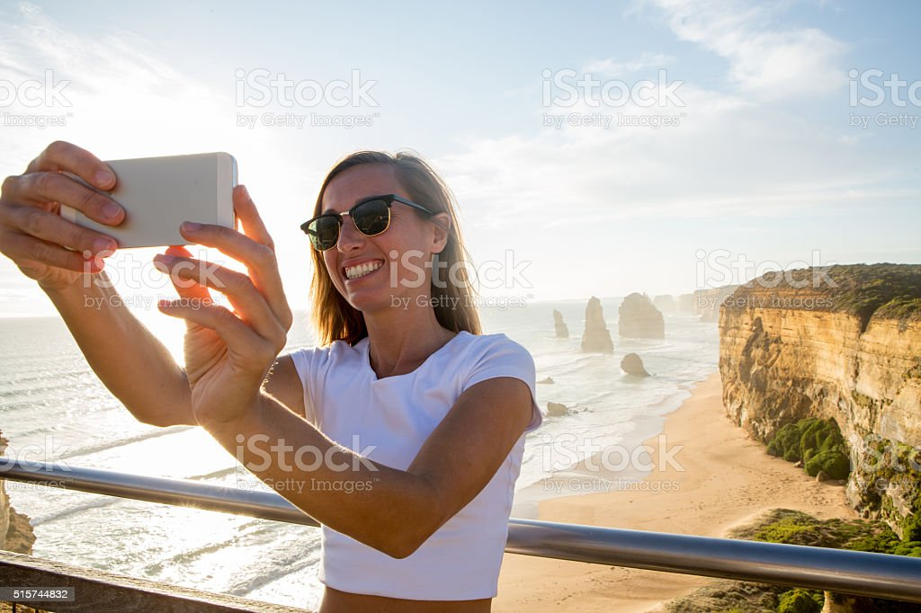 Young woman takes selfie portrait by the Twelve Apostles stock photo