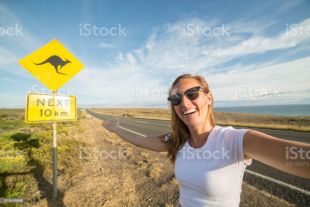 Young woman takes selfie portrait with warning road sign-Australia stock photo