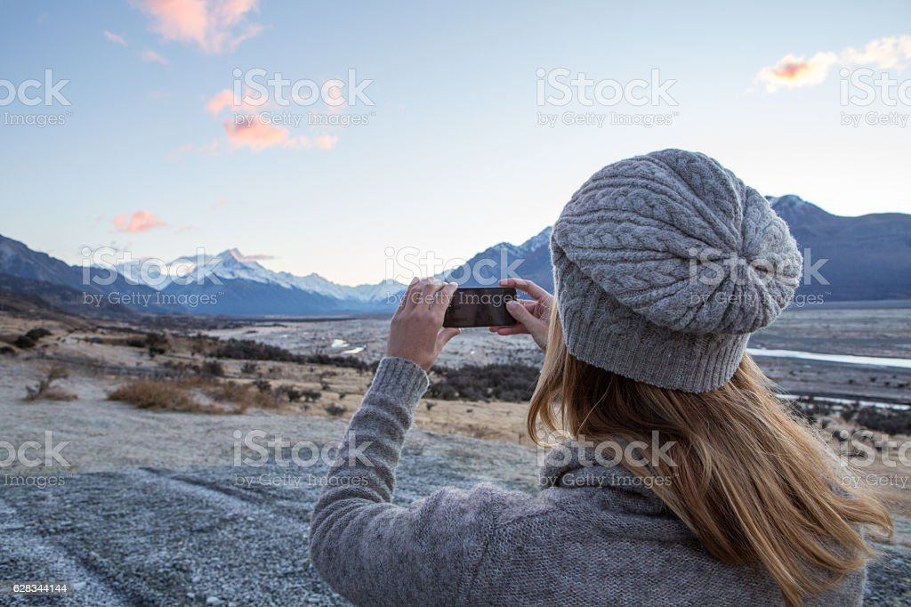Young woman takes smart phone picture of Mount Cook stock photo