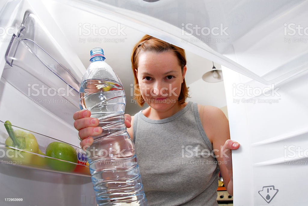 Young woman taking a bottle of water from the fridge stock photo