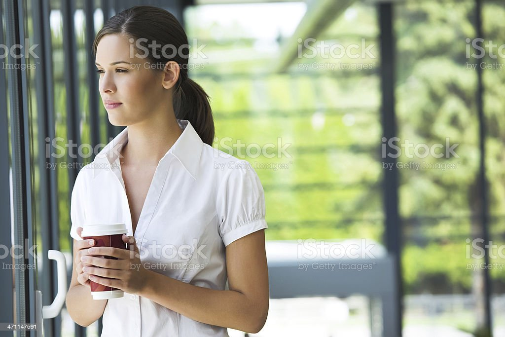 Young woman taking a coffee break at a city park royalty-free stock photo