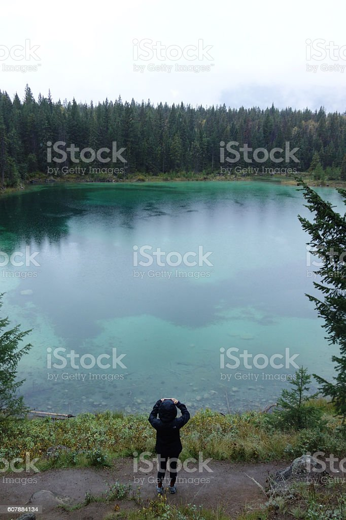 Young woman taking a photo of a turquoise lake stock photo
