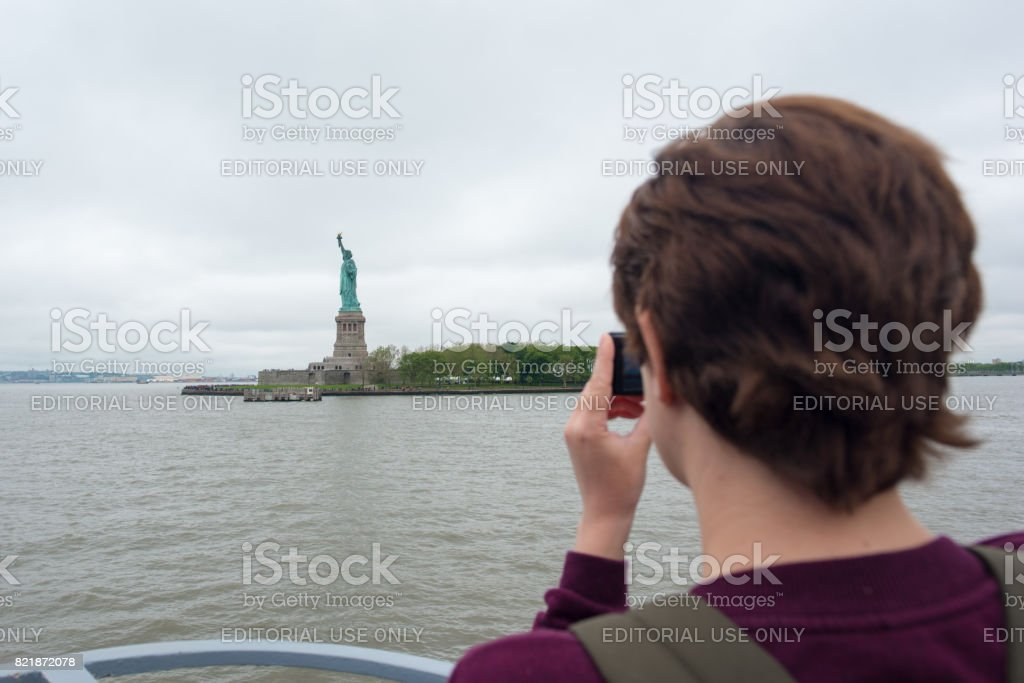 Young woman taking a photo of the Statue of Liberty stock photo