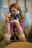 Young woman taking a photo with retro digital camera.