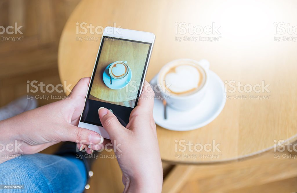 Young woman taking a picture of a coffee cup stock photo