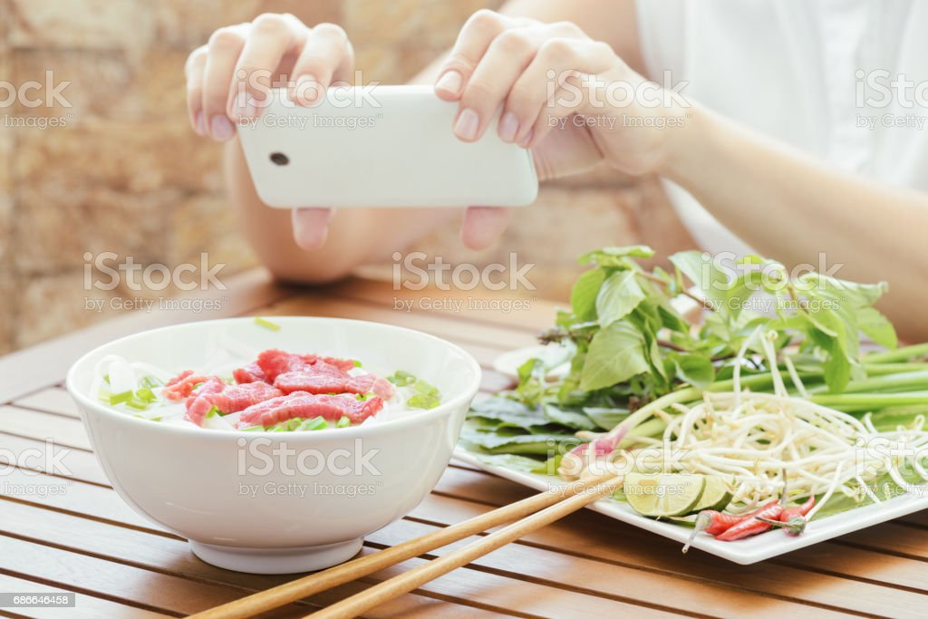 Young woman taking a picture the Pho Bo on a smartphone, Vietnam stock photo