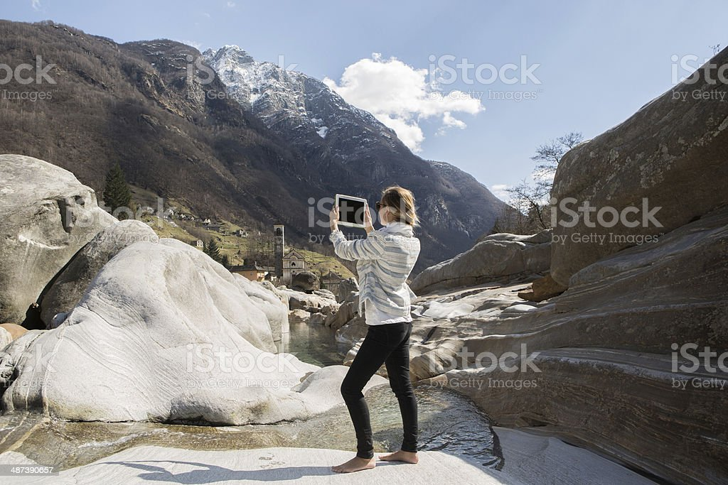 Young woman taking a picture with digital tablet in nature royalty-free stock photo