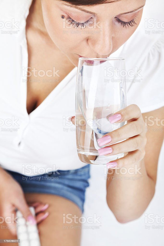 Young woman taking a pill stock photo