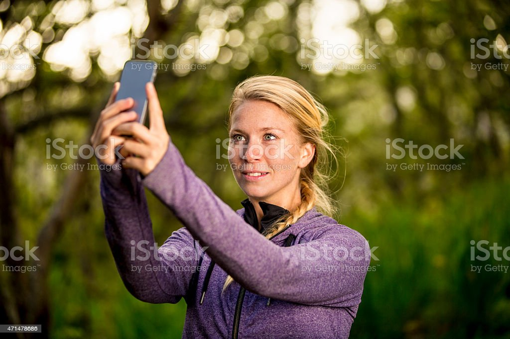 Young Woman Taking a Selfie in a Beautiful Nature Setting stock photo