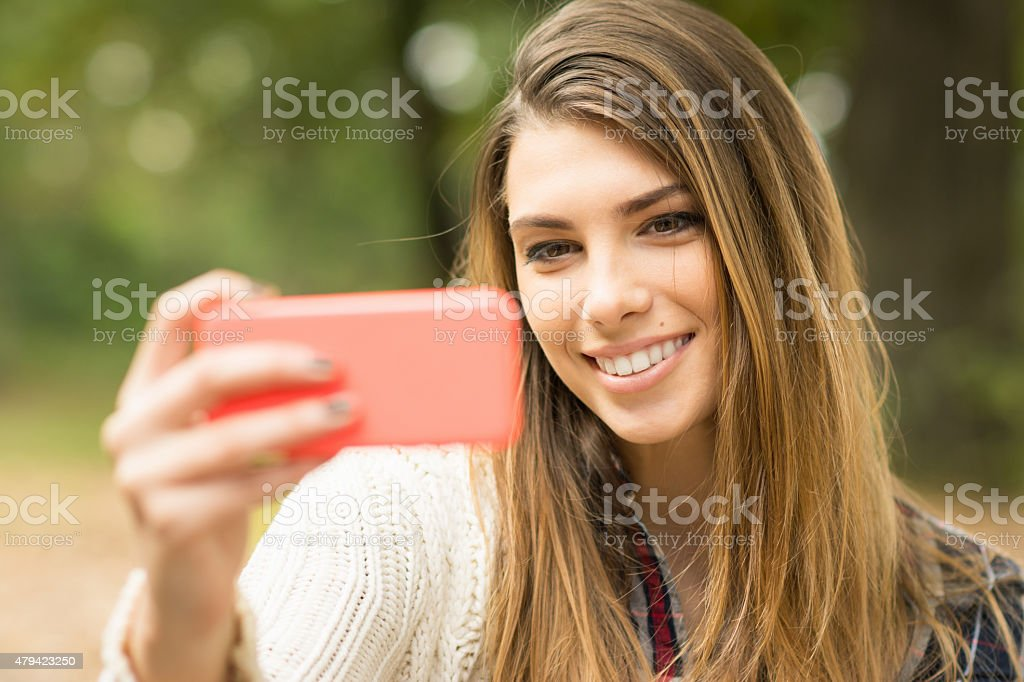 Young woman taking a selfie outdoors in autumn. No retouch stock photo