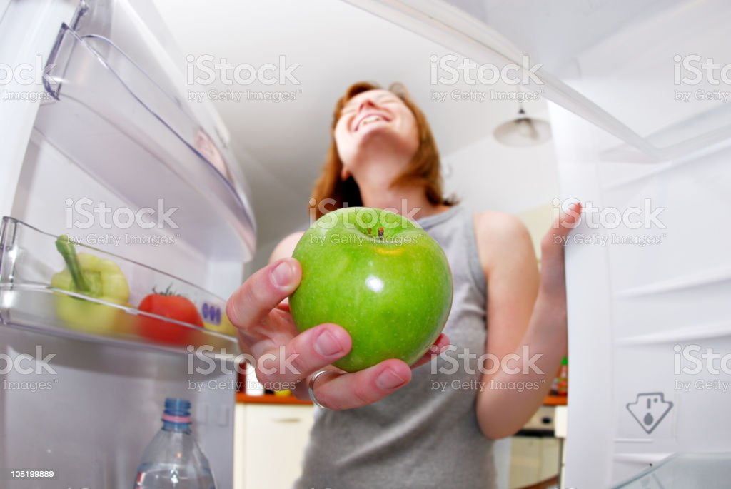 Young woman taking an apple from the fridge royalty-free stock photo