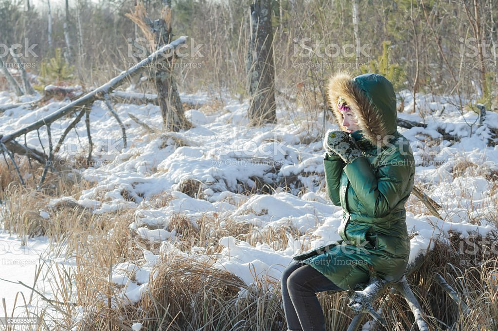 Young woman taking break in winter snowy forest outdoors stock photo