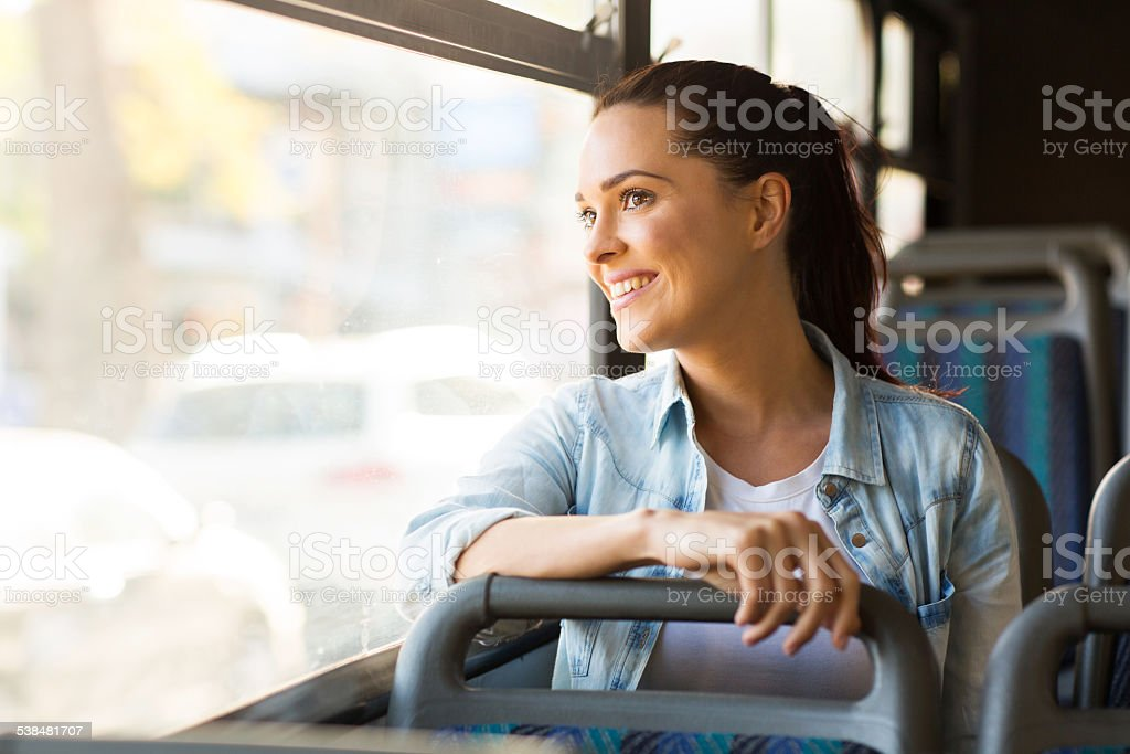 young woman taking bus to work stock photo