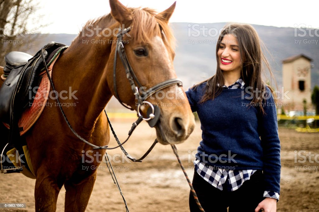 Young woman taking care of her horse stock photo
