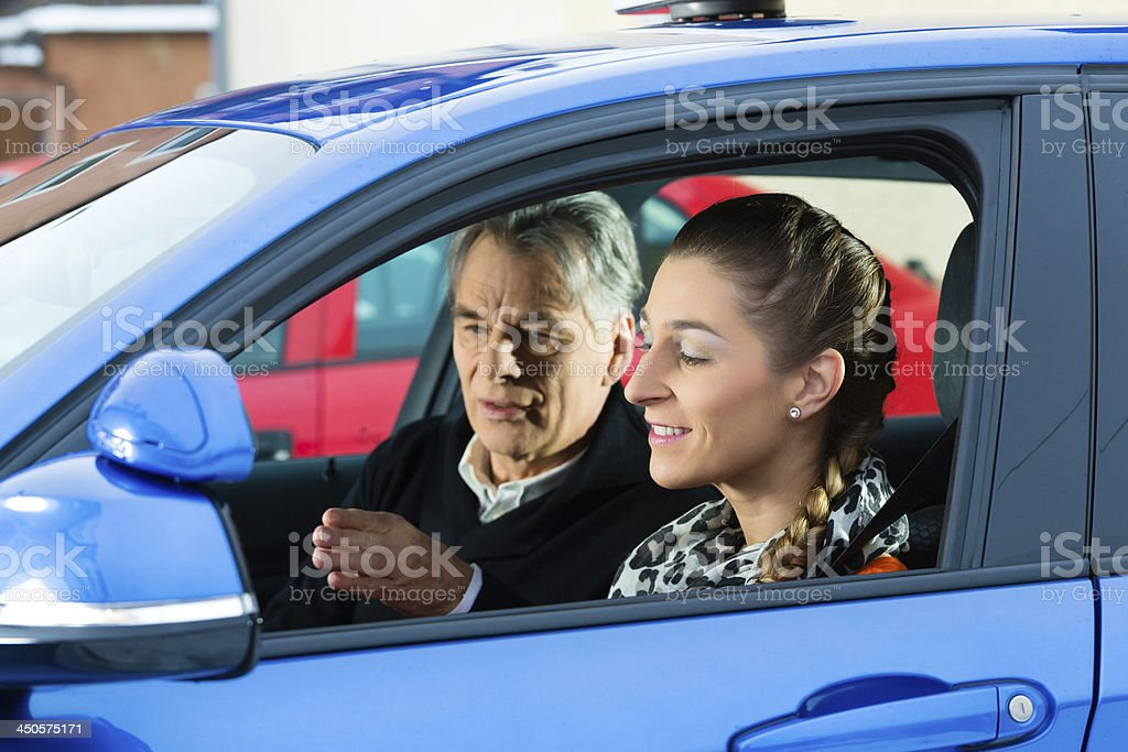Young woman taking instructions from her driving instructor stock photo