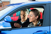 Young woman taking instructions from her driving instructor