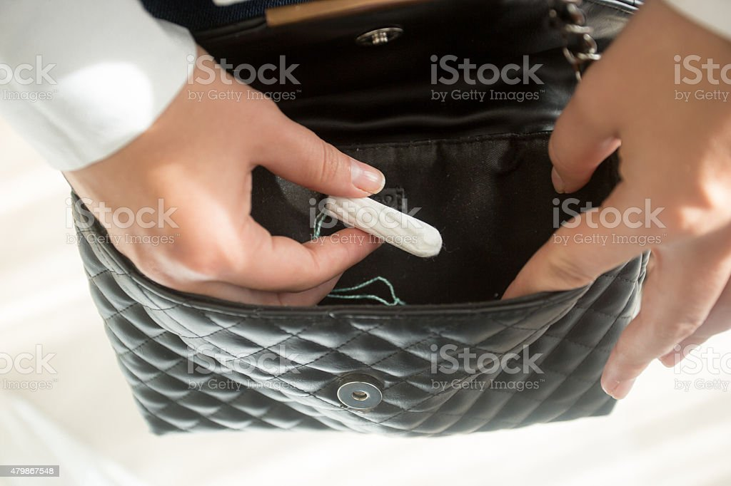 young woman taking menstrual tampon from purse stock photo