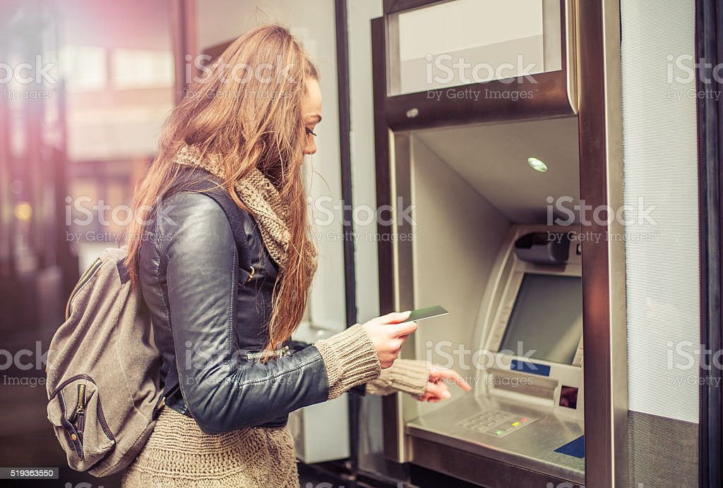 Young woman taking money from ATM royalty-free stock photo