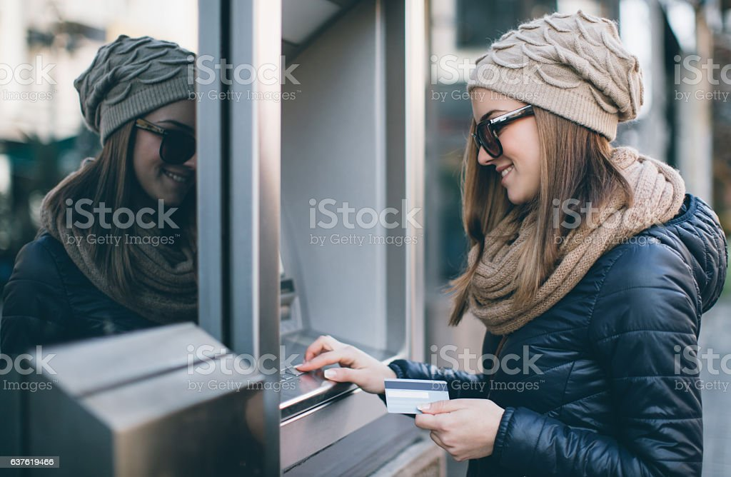 Young woman taking money from ATM stock photo