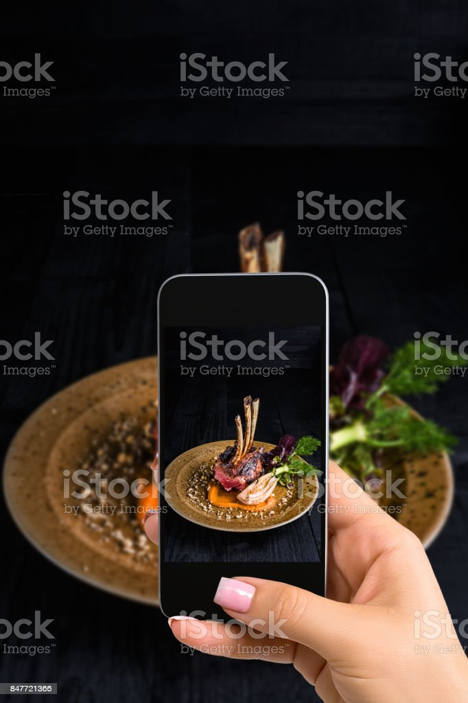 A young woman taking photo of food on smartphone, photographing meal with mobile camera stock photo