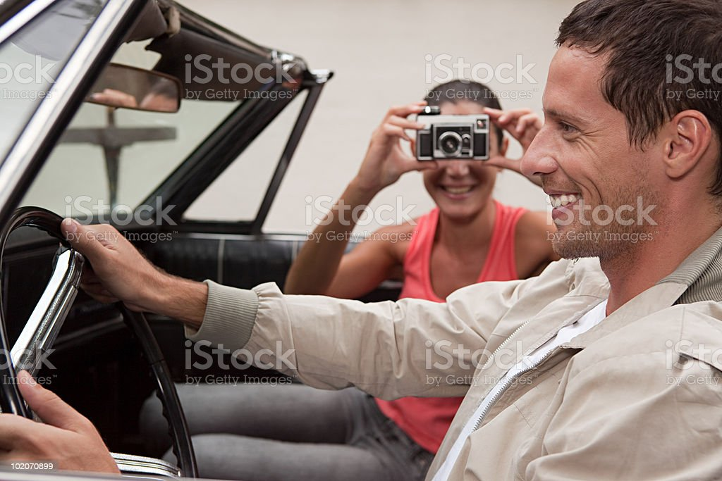 Young woman taking photograph of man in convertible car royalty-free stock photo