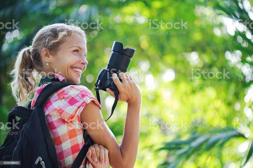 Young woman taking photos with camera stock photo
