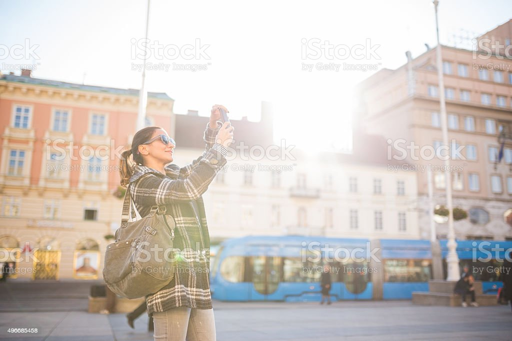 Young woman taking photos with mobile phone on the street stock photo