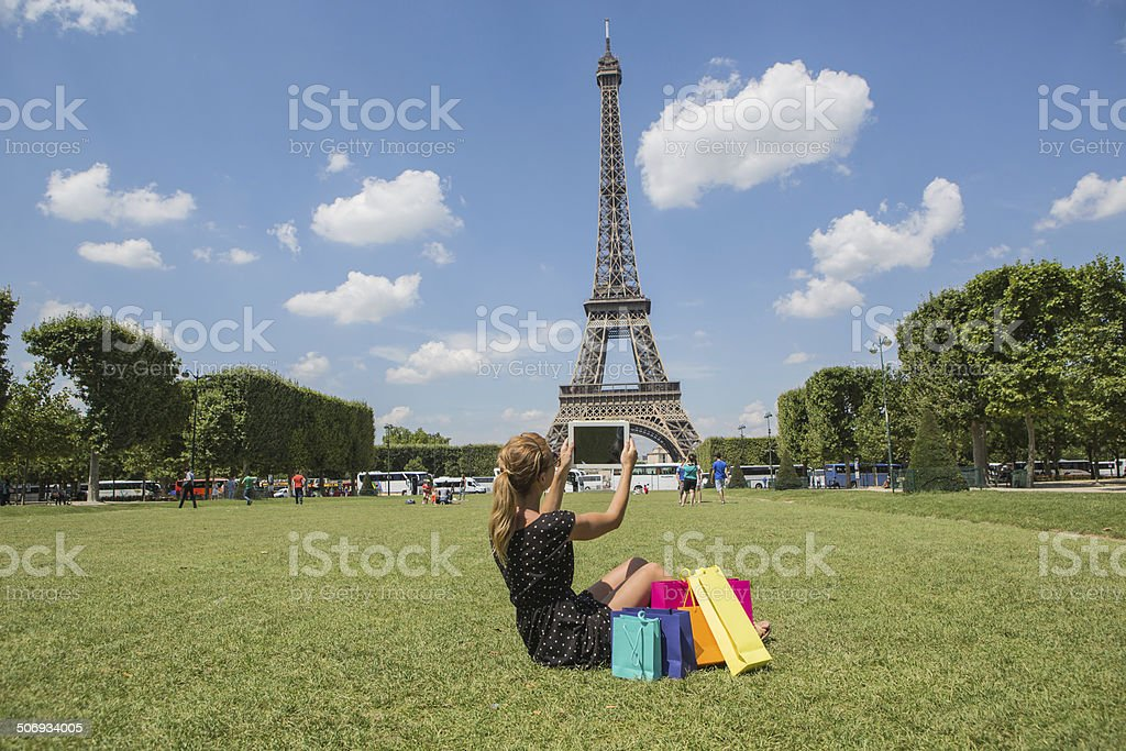Young woman taking picture of Eiffel tower with digital tablet royalty-free stock photo