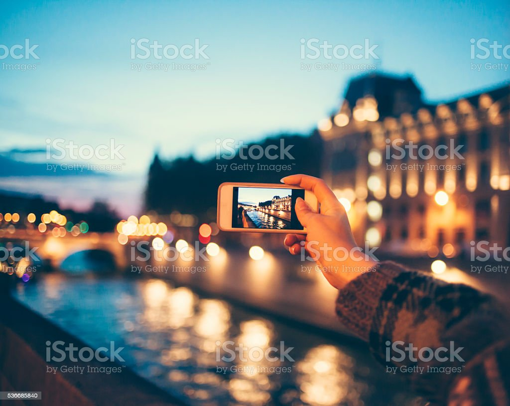 Young woman taking picture of river bridge by night stock photo