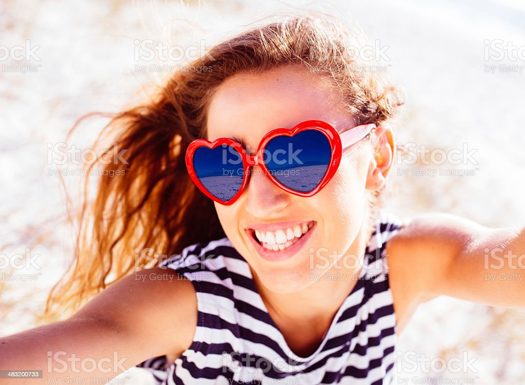 Young woman taking selfie at the beach stock photo