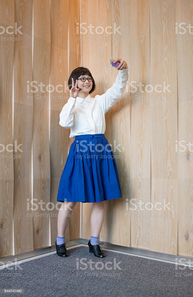 Young woman taking selfie by wooden wall. stock photo
